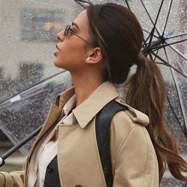 Mujer sosteniendo una parte de su cabello pelirrojo con la mano izquierda, mirando a la cámara.