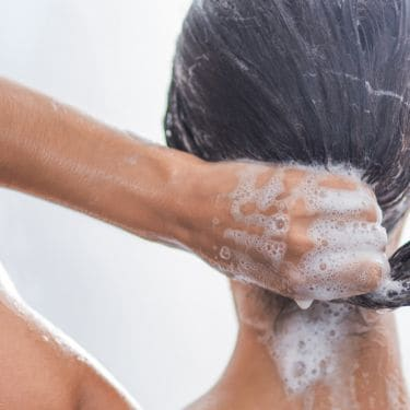 Woman lathering shampoo into hair