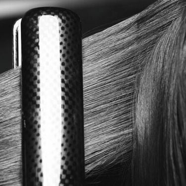 A section of long dark, damaged hair being styled with a flat iron