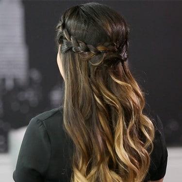 عارضة ذات شعر بني طويل مع تسريحة تاج المجدلة.