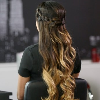 A model with long brown hair styled into a braided crown.