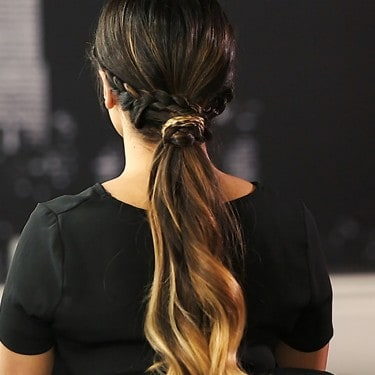 Model's hair styled into a braided low ponytail.