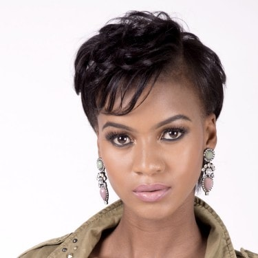 Model with short dark brown hair, dark skin tone and large hanging stone earrings.