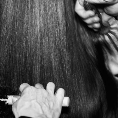 Black and white shot of the back of a woman's head with hands of a stylist with a brush and hair dryer and another stylist's hands holding a brush; both styling her hair