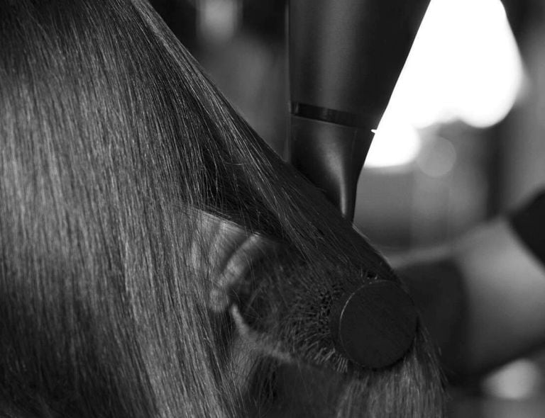 Close up of a model's hair being styled with a brush and blow dryer.