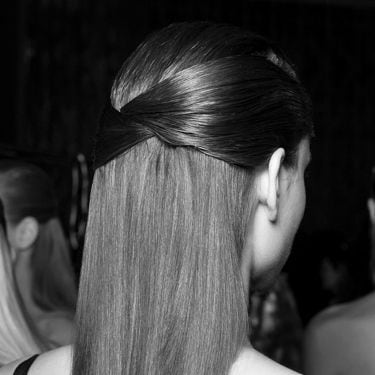 A model with the side sections of her hair gathered around the back of her head.