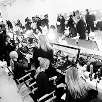 Backstage at a fashion show. The room buzzes with models, stylists, photographers, styling tools and hair products.