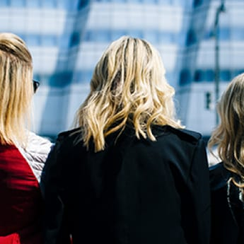 Three blonde women standing on a busy city street