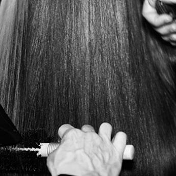 Close up of heat tongs being applied to a section of long dark hair.