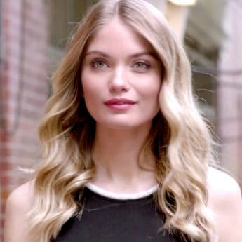 A blonde model walking down the street with her hair in loose waves