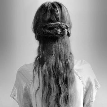 The back of a woman's head and shoulders. She wears her light brown hair in a messy, plaited bun.