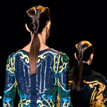 Photo of a models on the catwalk with their back to the camera, wearing colourful dresses with their hair in ponytails
