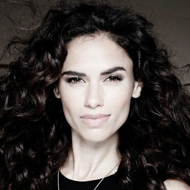 A woman holding her thick, curly dark brown hair and smiling directly to camera.