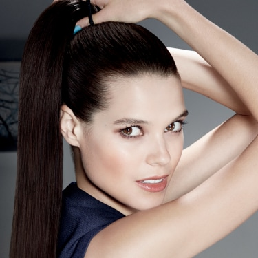 A woman putting her hair into a high pony tail whilst looking directly into the camera