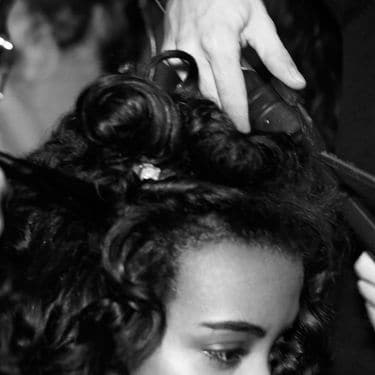A model has her curly hair worked on by two stylists using heat tongs and other styling tools.