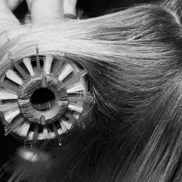 Close-up of a model's fine hair being styled with a brush and blow-dryer