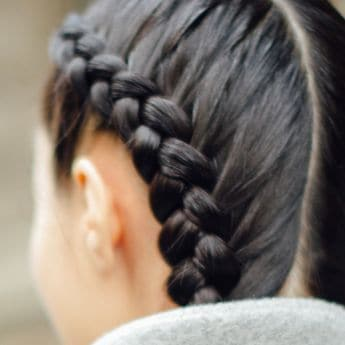 a model with dark brown hair in two thick braids along each side of her head