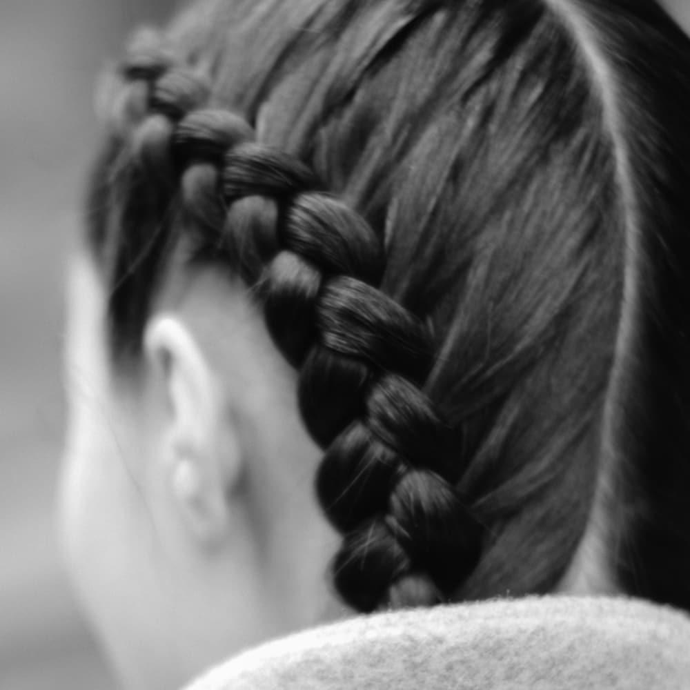 Una modelo con el cabello castaño oscuro recogido en dos trenzas gruesas