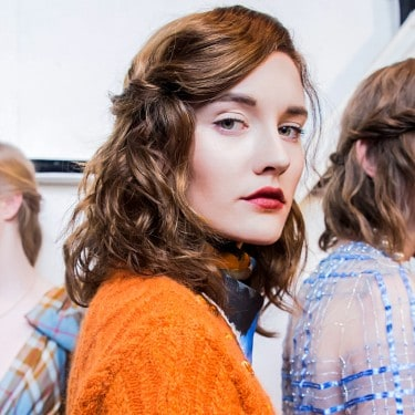 Models lined up with beautiful hairstyles, one looking at the camera