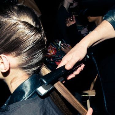 A hairdresser using a heat styling tool on a section of a model's hair