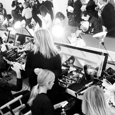 Models sitting in front of mirrors with hair stylists, photographers, styling tools and hair products