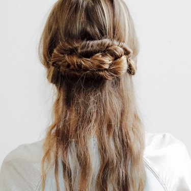 A model with her hair in a messy, plaited bun