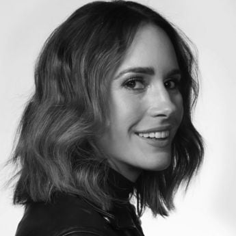 Close up of Louise Roe smiling at the camera, wearing a black leather jacket with a shoulder length wavy bob hairstyle