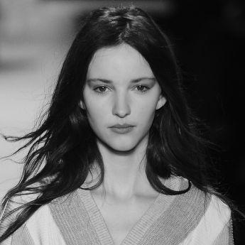 a model on the runway, with long dark brown hair, wearing a grey and white v-neck top