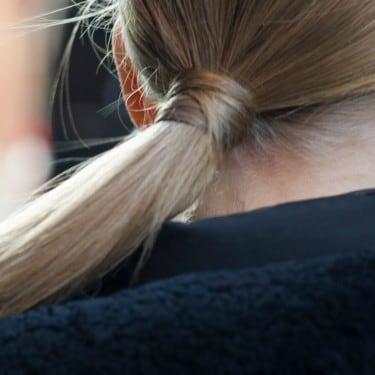 La parte posterior de la cabeza de una mujer con una larga cola de caballo rubia