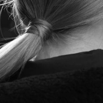 Close up of the back of a woman's head with a long blonde ponytail