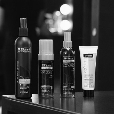 A selection of TRESemmé hair styling products, including hair serum and texturizing sprays.